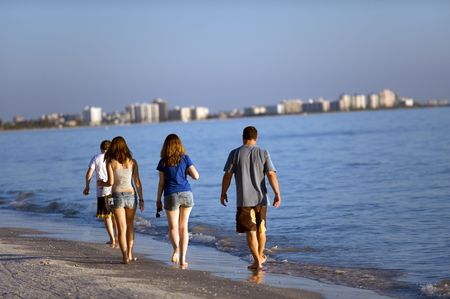 Young people strolling along Florida beach in Fort Meyers photo