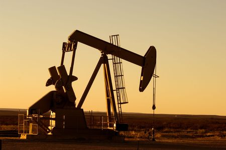 west texas: Working oil pump in rural Texas at sunset
