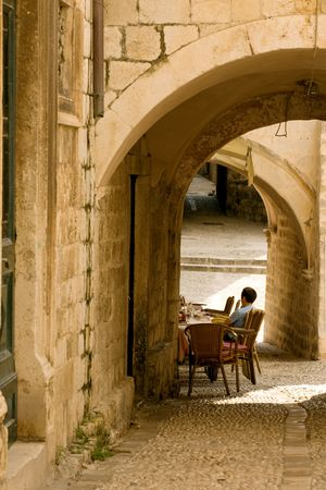 Tourist sitting in sidewalk cafe in historic Dubrovnik Stok Fotoğraf