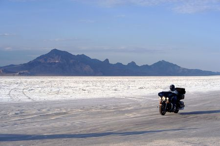 ut: Biker driving across Bonneville Salt Flats, Utah