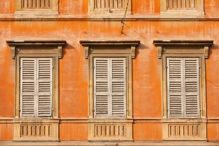 a window on the world: Colorful facade of old Modena building, Italy Stock Photo