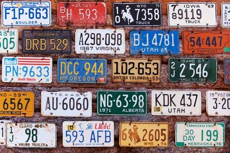 UTAH, ÉTATS-UNIS - 16 novembre 2008: Diverses anciennes plaques d'immatriculation américaines venant de différents Etats sur le mur du bâtiment en briques dans les régions rurales Utah Banque d'images - 10558588