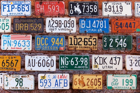 vintage: UTAH, UNITED STATES - NOVEMBER 16, 2008: Various old American license plates from different states on the wall of brick building in rural Utah