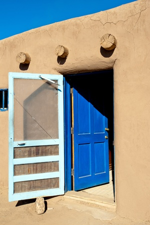 the dwelling: Bright blue door to the room of Taos Pueblo dwelling Stock Photo