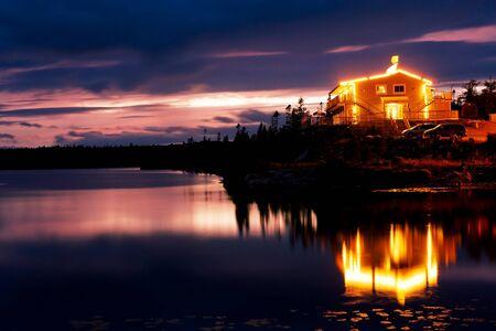 Illuminated lakeside motel in the wilderness of Nova Scotia Stock Photo