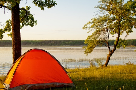 campsite: Bright tent by the picturesque lake around sunset