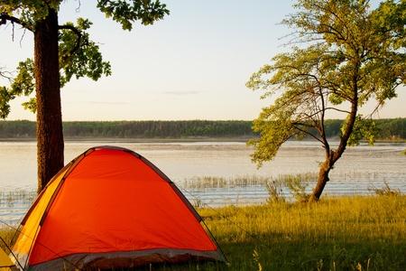 Helle Zelt durch den malerischen See bei Sonnenuntergang Standard-Bild - 9726676
