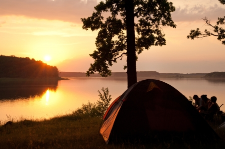 Camping by the picturesque lake at sunset