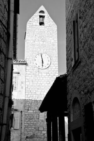 Clock tower on narrow street in old Rab town, Croatia photo