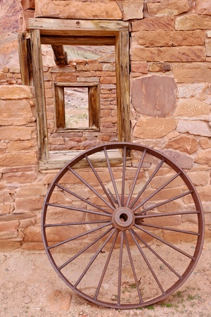 A wheel in front of historic building at Lees Ferry photo