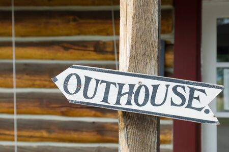 outhouse: Outhouse sign in front of roadhouse, Alaska Stock Photo