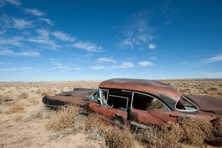 Old rusted car in the middle of New Mexico desert photo