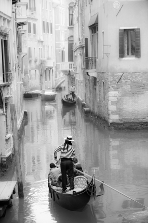 Gondolier guiding a gondola in narrow Venetian canal photo