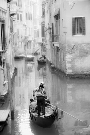 Gondolier guiding a gondola in narrow Venetian canal