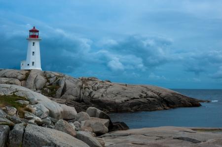 fishing village: Peggys Point Lighthouse at sunset, Nova Scotia Stock Photo
