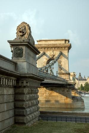 Guardian lion statue on famous Chain Bridge across Danube in Budapest