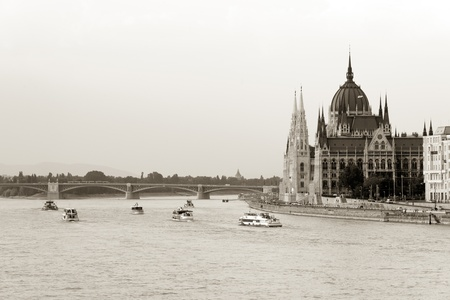 Boats cruising by Parliament building in Budapest photo