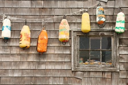 Colorful buoys on the old house in Peggys Cove, Nova Scotia photo