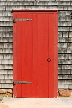 cape cod home: Wooden red door of the traditional New England house
