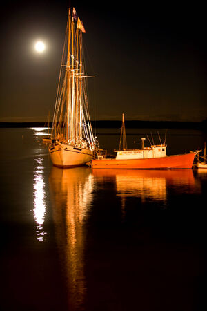 Sailing ship and fishing boat in Bar Harbor, Maine in the moonlight photo