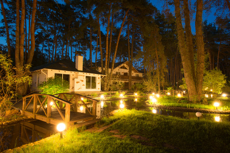 guest house: Cozy resort by the lake in the conifer forest at night Editorial