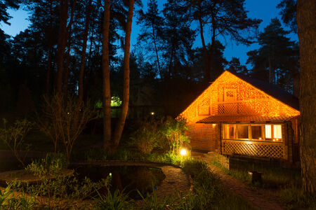 rural development: Cozy houseby the pond in the conifer forest at night Editorial