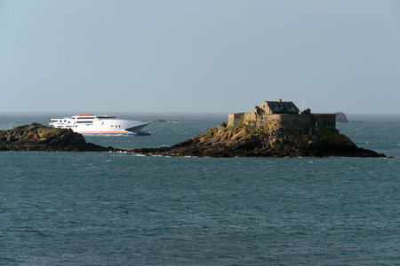 Ferry sailing past Harbour Island fort near Dinard, Brittany photo