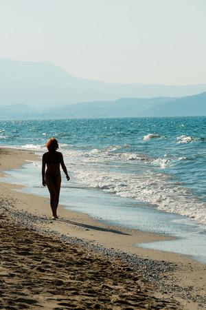 strolling: Woman strolling on sandy beach of Crete shore, Greece