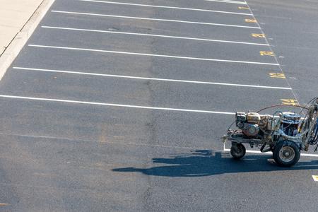 Werknemer met een striping die verse lijnen schildert op de parkeerplaats voor ontwikkeling, VS
