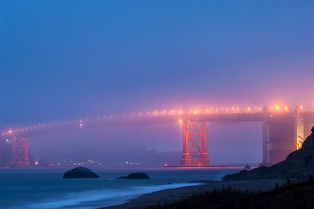 Golden Gate bridge at foggy night viewed from Baker Beach, San Francisco, California