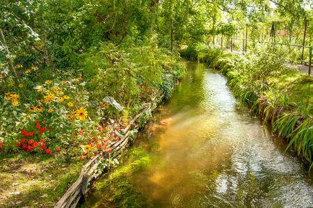Flusso d'acqua che attraversa il famoso giardino di Claude Monet a Giverny, Normandia, Francia