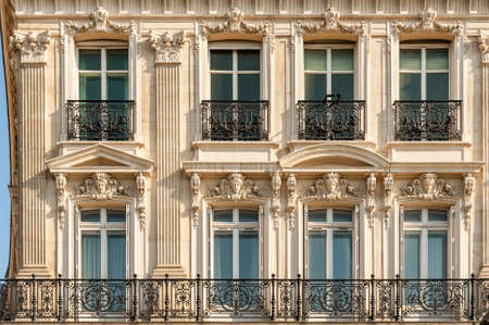 Facade of one of the beautiful buildings along Champs Elysees avenue with typical wrought iron fences and modeling, Paris, France