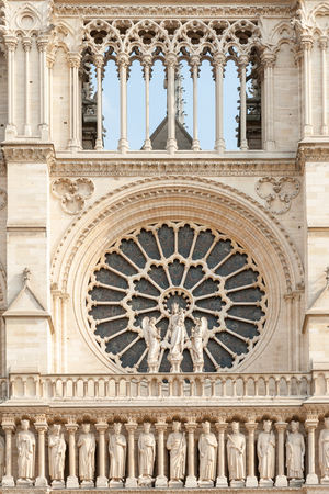 Close up of Notre Dame de Paris cathedral facade with rose window and row of stone statues in Paris, France