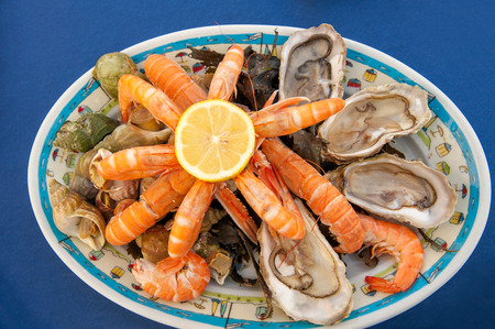 Plateau de fruits de mer, traditional French seafood plate of raw and cooked shellfish such as oysters, prawns, shrimp, and periwinkle served in seaside restaurant