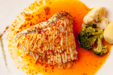 French popular Aile de Raie (skate wing) fish plate with sauce and potato and broccoli on a side