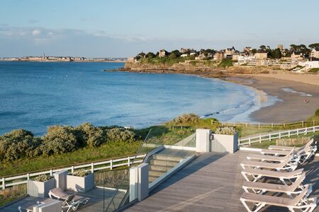 Sunbeds and sandy beach in Dinard, famous holiday destination on Breton coastline, with Saint-Malo in the distance, Brittany, France Stock Photo