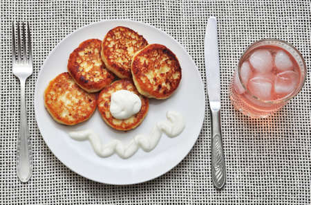 sapid: cottage cheese pancakes with a cold drink Stock Photo