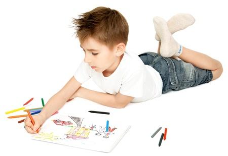 De jongen, liggend op de vloer, tekent en schildert zijn favoriete foto