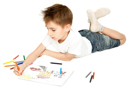 The boy, lying on the floor, draws and paints his favorite picture