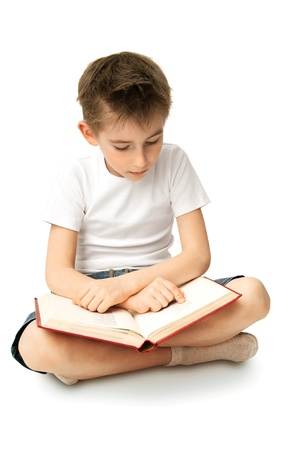 seven year old: A boy sitting on a floor and reading  big book
