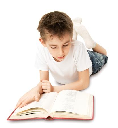 ni�os leyendo: El ni�o acostado en el piso y leyendo un libro grande Foto de archivo