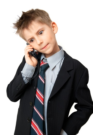 understanding: Cute  Boy in Suit talking on a cell phone over a white background Stock Photo