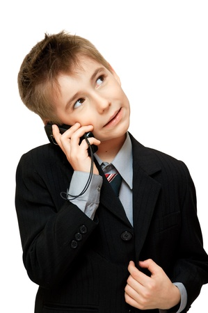 Cute  Boy in Suit talking on a cell phone over a white background photo