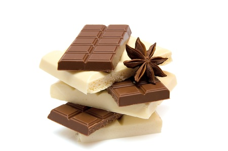 slices of black and white chocolate with anise on white background photo