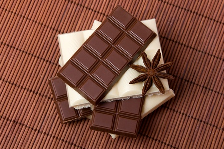 slices of black and white chocolate with anise on dark background photo