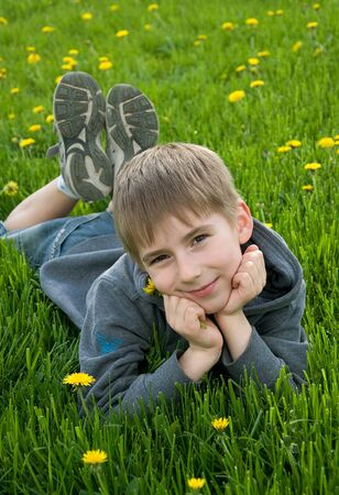 8 years old: eight years old boy lying on dandelion meadow Stock Photo