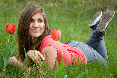 young girl lying on the grass in the garden near the tulips photo