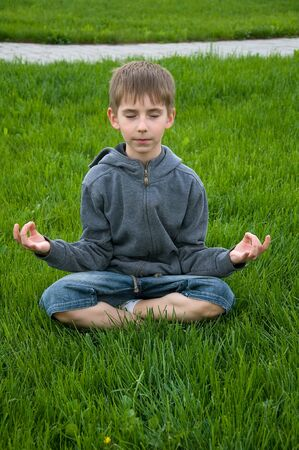 boy practices yoga outdoors photo