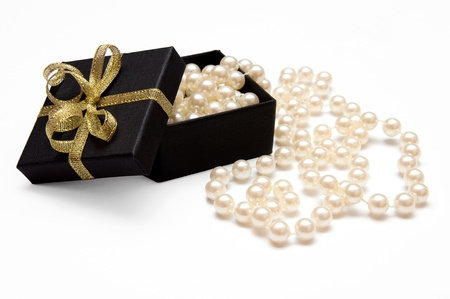 Gift box with golden ribbon and pearl beads isolated on white background photo