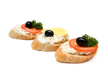 Mini sandwiches - bread with cream cheese, tomato, lemon, olives and parsley